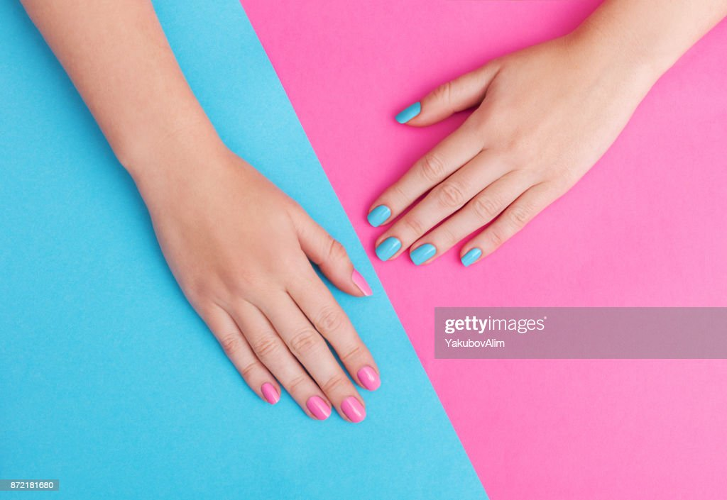 Closeup of hands of a young woman with manicure on nails against pink background : Stock Photo