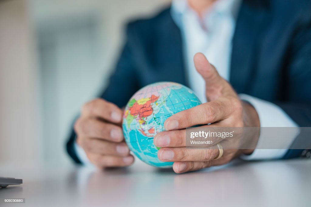 Close-up of hands of businessman holding globe : Stock Photo