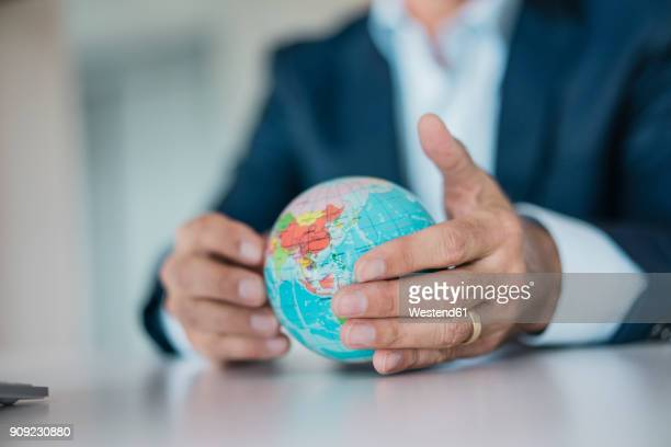 close-up of hands of businessman holding globe - global stock-fotos und bilder