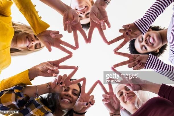 Close-up of hands of five women shaping a star