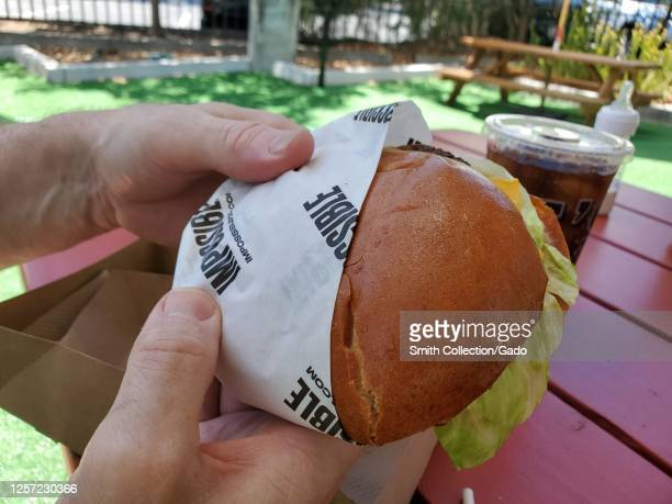 Closeup of hands of mature man holding Impossible brand vegan burger with logo visible Walnut Creek California July 8 2020