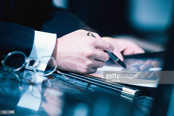 Close-up of hands on desktop, holding pen and magazine