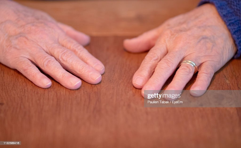 Close-Up Of Hands On Table : Stockfoto
