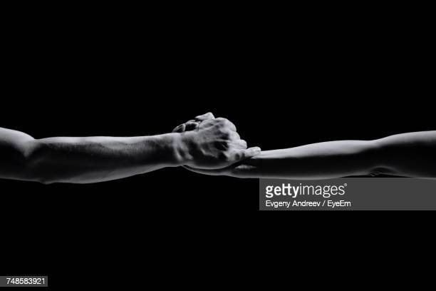 close-up of hands over black background - kracht stockfoto's en -beelden