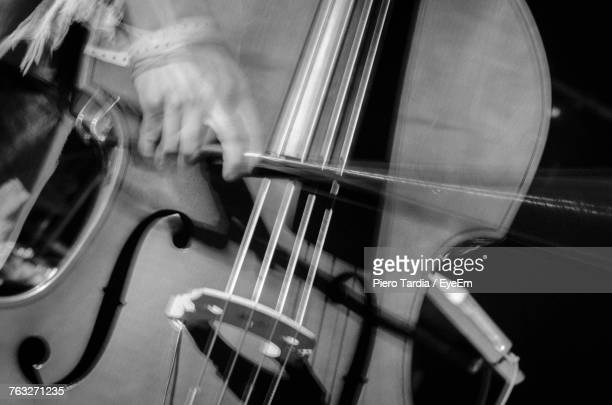 Close-Up Of Hands Playing Double Bass