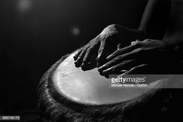 close-up of hands playing drum against black background - percussion instrument stock photos and pictures