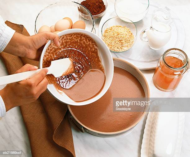 close-up of hands pouring batter into a baking dish on a table top