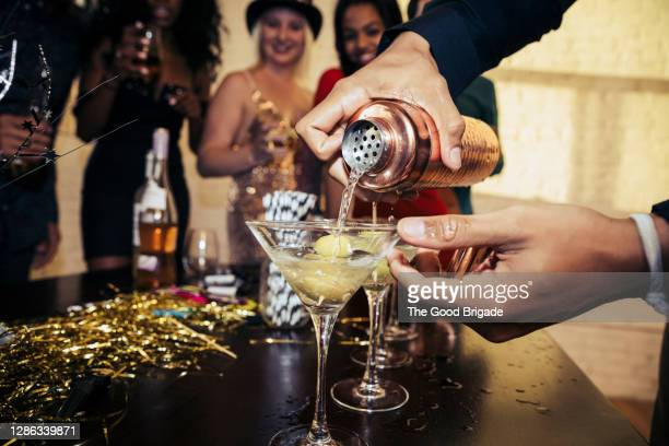 close-up of hands pouring drink in martini glass at party - refreshment stock pictures, royalty-free photos & images