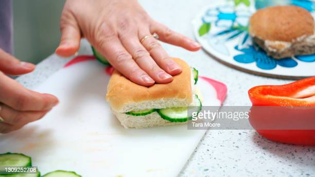 closeup of hands preparing bread roll - chopping stock pictures, royalty-free photos & images