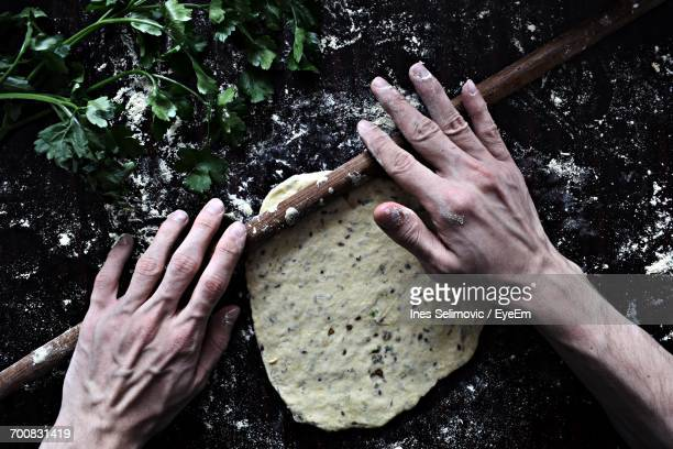 Close-Up Of Hands Rolling Dough