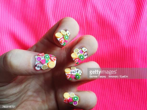 Close-Up Of Hands Showing Fruit Themed Nail Art