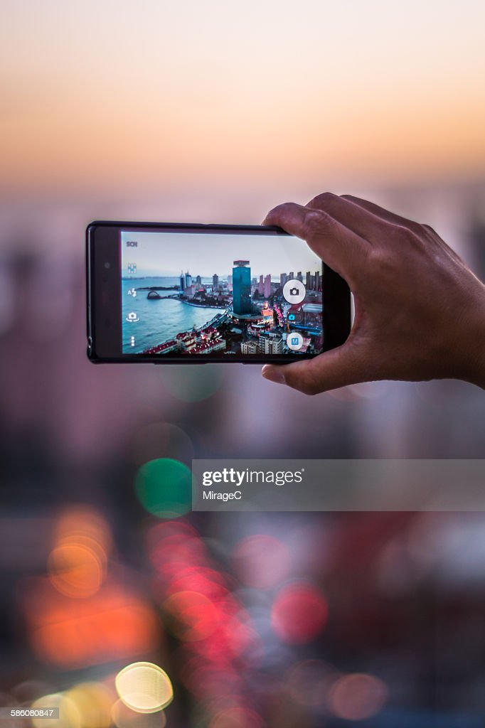 Close-up of hands taking picture of city skyline : Stock Photo