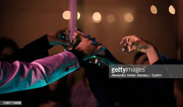 close-up of hands toasting shot glasses in night club - human body part stock pictures, royalty-free photos & images