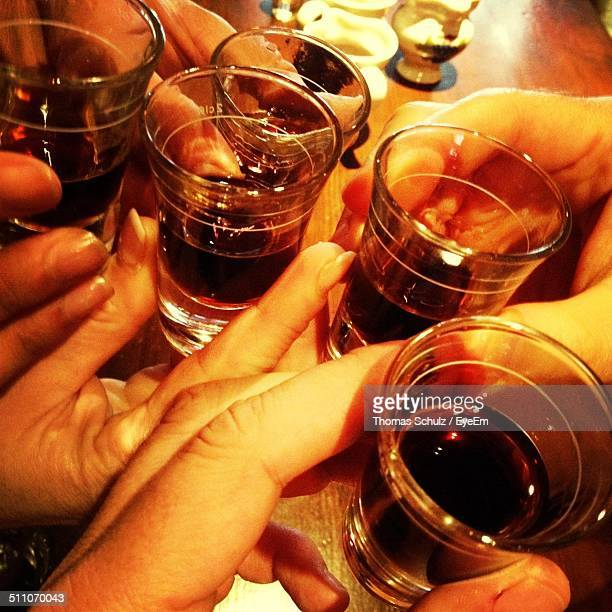 Close-up of hands toasting tequila shots in a nightclub