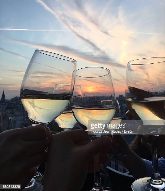 Close-Up Of Hands Toasting Wine Glasses Outdoors