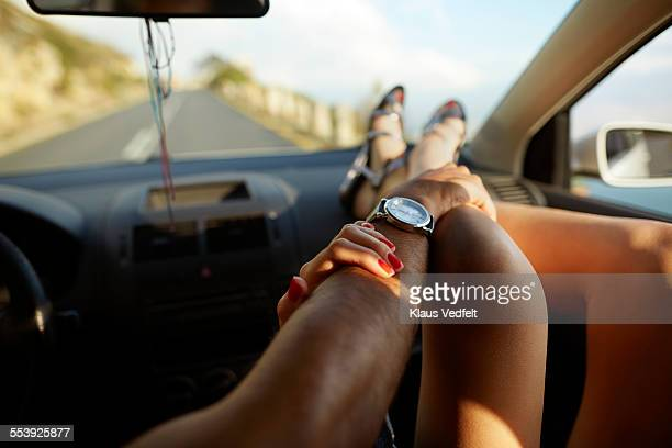 Close-up of hands touching arm and leg inside car