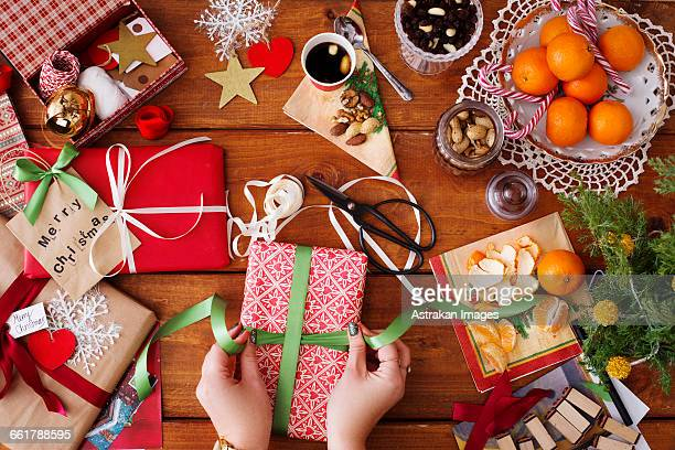 Close-up of hands tying ribbon on Christmas gift at wooden table