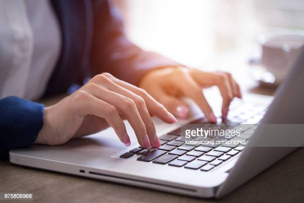 Close-up of hands typing on laptop keyboard in the office.
