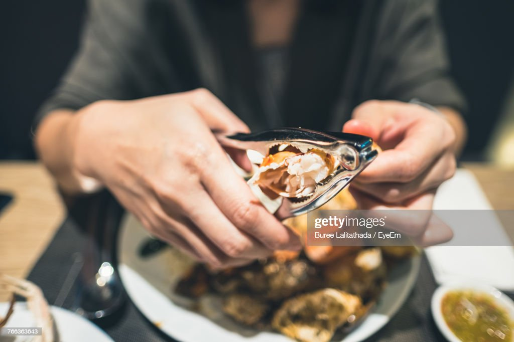 Close-Up Of Hands Using Pliers For Seafood : Stock Photo