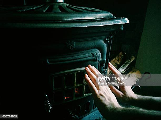close-up of hands warming by fireplace during winter - wood burning stove stock photos and pictures