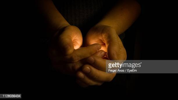 close-up of hands with illuminated light against black background - main tendue photos et images de collection