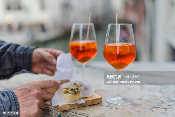 close-up of hands with snacks and cocktails - antipasto stock photos and pictures