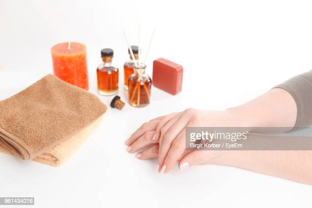 Close-Up Of Hands With Towel And Oil Bottles Over White Background