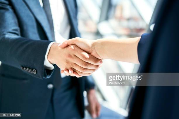 close-up of handshake of businesswoman and businessman - abmachung stock-fotos und bilder