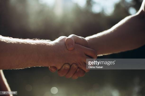 close-up of handshake of two men when they meet - final game stock pictures, royalty-free photos & images