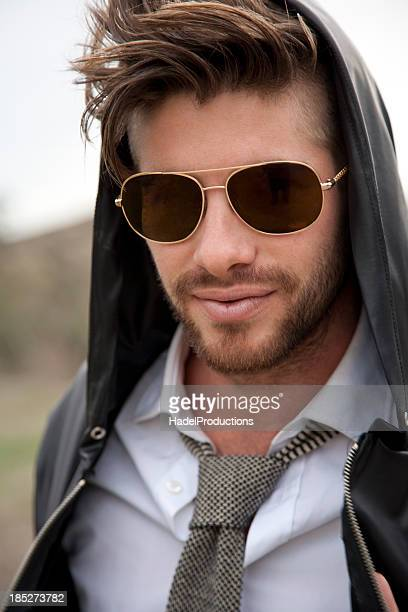 Close-up of handsome male model wearing a pair of sunglasses