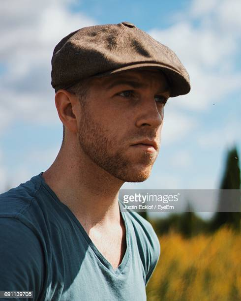 close-up of handsome man against sky - flat cap stock pictures, royalty-free photos & images