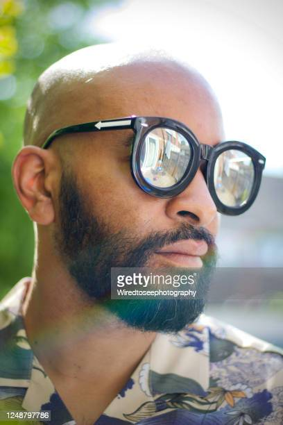 close-up of handsome man standing in garden wearing sunglasses - social justice concept stock pictures, royalty-free photos & images