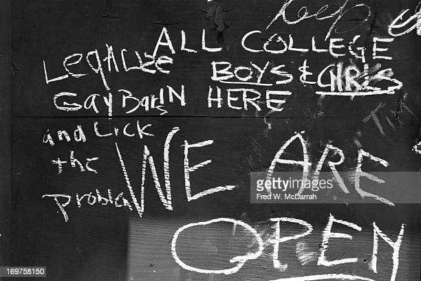 Closeup of handwritten chalk text on a boardedup window of the Stonewall Inn after riots over the weekend of June 27 1969 The text reads 'We Are...