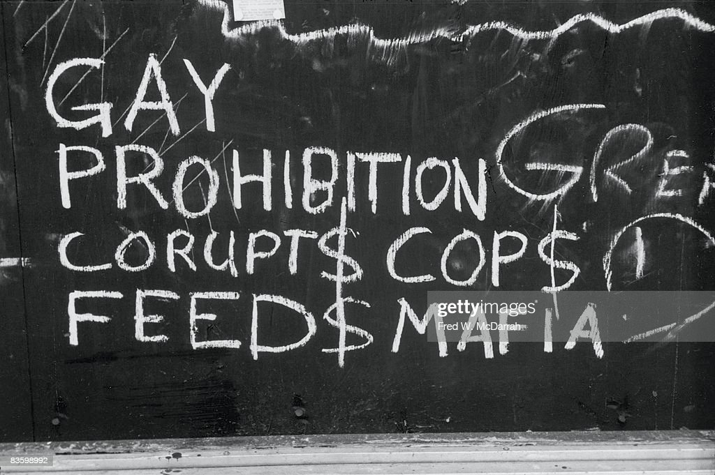 Close-up of handwritten chalk text on a boarded-up window of the Stonewall Inn (53 Christopher Street) after riots over the weekend of June 27, 1969. The text reads 'Gay Prohibition Corupts (sic) Cops and Feeds Mafia' and refers to payoffs made to police officers by the owners of gang-operated, then-illegal gay bars. The bar and surrounding area were the site of a series of demonstrations and riots over the weekend that led to the formation of the modern gay rights movement in the United States.