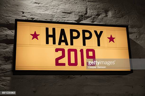 Close-up of Happy 2019 signboard against gray wall