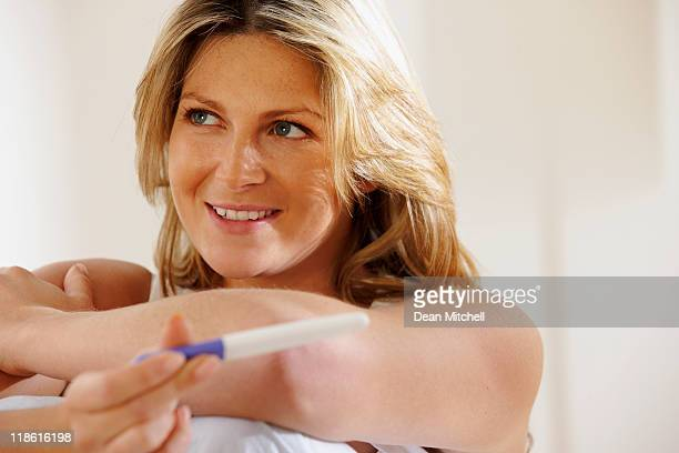 close-up of happy attractive woman checking pregnancy test at home