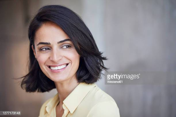 close-up of happy businesswoman contemplating against wall in office - black hair stock pictures, royalty-free photos & images