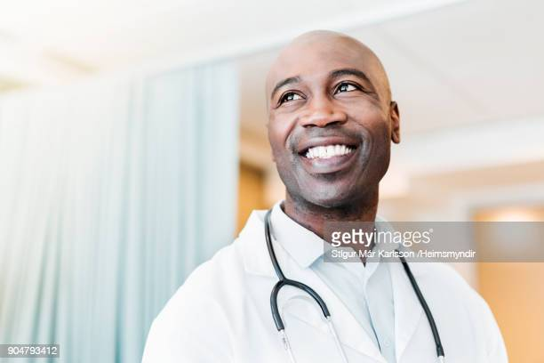 Close-up of happy confident doctor looking away