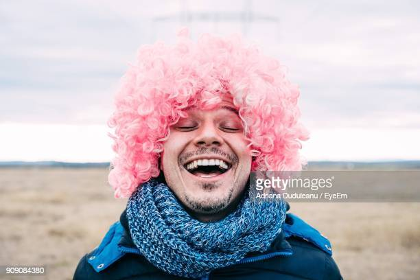 Close-Up Of Happy Man Wearing Wig At Beach Against Sky