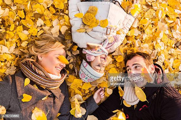 close-up of happy parents and daughter among autumn leaves. - girl mound stock pictures, royalty-free photos & images