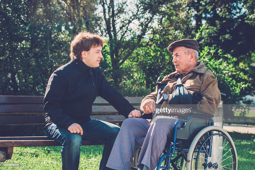 Close-Up of Happy Senior Man in Wheelchair and Grandson Outdoors : Stock Photo