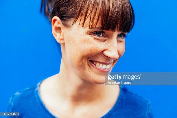 Close-up of happy woman looking away against blue background