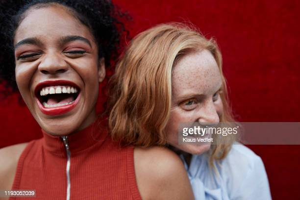 close-up of happy young females standing outdoors - lachen stock-fotos und bilder
