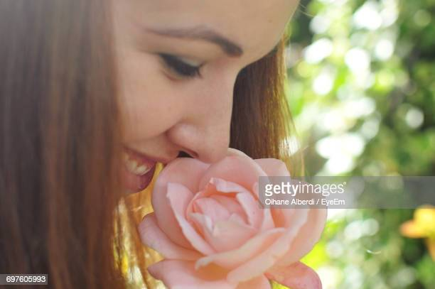 Close-Up Of Happy Young Woman Smelling Pink Rose