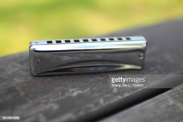 Close-Up Of Harmonica On Wooden Plank