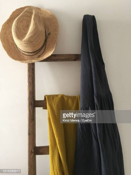 close-up of hat hanging on ladder against wall at home - ブリンディシ ストックフォトと画像
