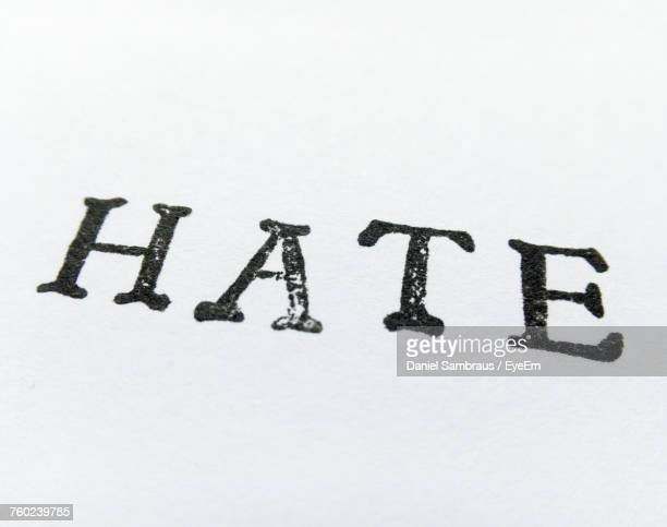 Close-Up Of Hate Text On White Paper
