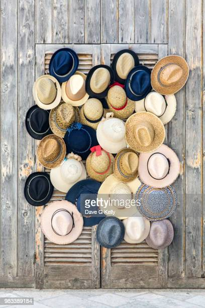 close-up of hats hanging for sale at market - polignano a mare stock photos and pictures