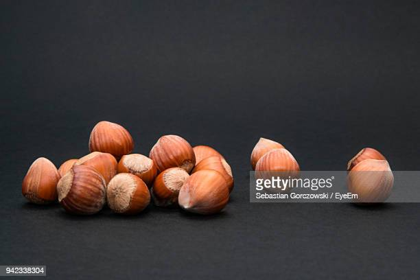 close-up of hazelnuts against black background - hazelnuts stock pictures, royalty-free photos & images