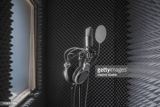 close-up of headphones on microphone stand in soundproof recording studio - sound recording equipment stock pictures, royalty-free photos & images